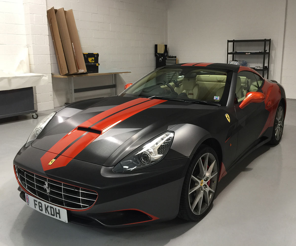 Ferrari California in workshop - grey, black, orange wrap